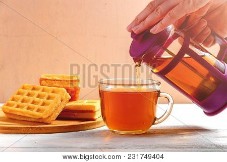 Female Hands Pour Tea From Brewer Into Mug On White Wooden Table With Waffles