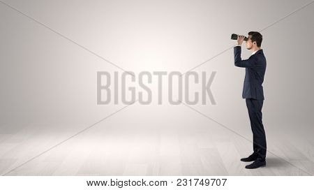 Businessman looking forward with binoculars in an empty space