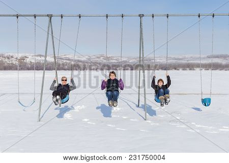 Horizontal Image Of Three Caucasian Women  Laughing As They Are Swinging On A Swing  In The Middle O