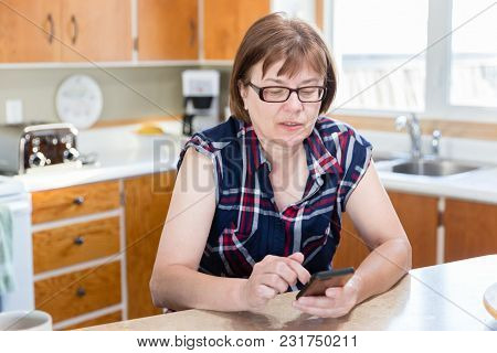 Horizontal Close Up Image Of A Caucasian Woman Sitting In Her Kitchen Using Her Cell Phone.