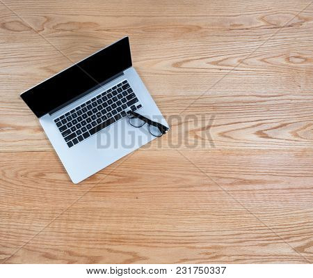 Clean Oak Wooden Desktop With Laptop Computer And Reading Glasses