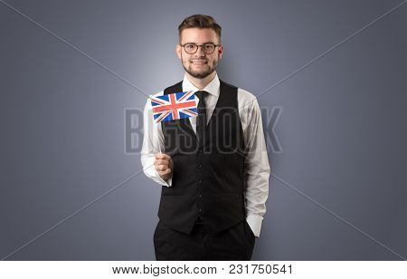 Cheerful student standing in front of wall with national flag on his hand