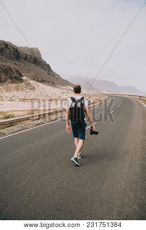 Traveler Walks In The Center Of An Epic Winding Road. Huge Volcanic Mountains In The Distance Behine