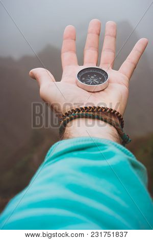 Hand With Compass On The Rock In Front Of The Monumental Mountain Range Silhouette In The Fog.