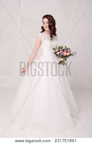 Beautiful Female Model In Long Fashionable Dress Standing With Bouquet Of Flower. Stylish Luxurious