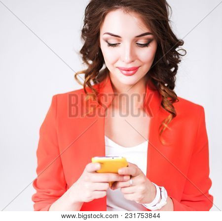 Beautiful businesswoman using cell phone standing in office