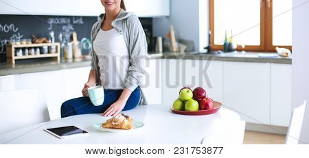 Young woman with orange juice and tablet in kitchen