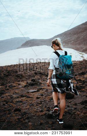 Woman Hiker Walking On Barren Rocky Terrain Among Black Volcanic Boulders And White Sand Dunes. Sao