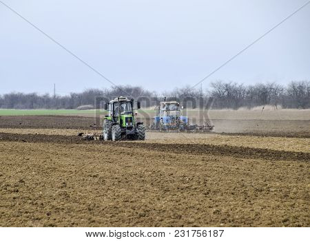 Lush And Loosen The Soil On The Field Before Sowing. The Tractor Plows A Field With A Plow.