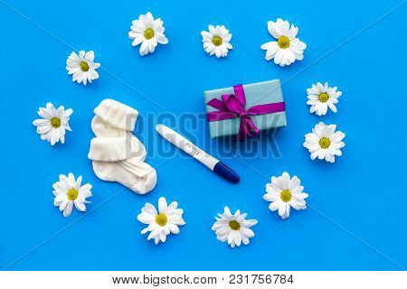 Pregnancy And Preparation For Childbirth. Pregnancy Test Near Flowers On Blue Background Top View Sp