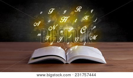 Glowing yellow alphabet letters coming out of an open book