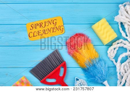 Accessories For Cleaning On Wooden Background. Yellow Paper Card With Text Spring Cleaning. Cleaning