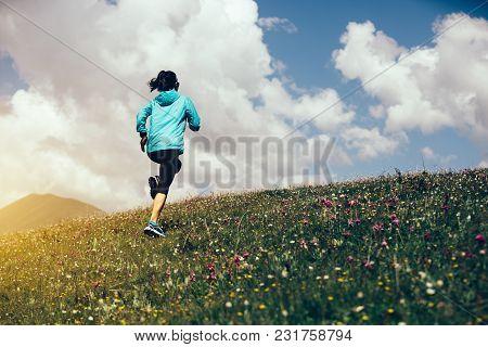 Young Fitness Woman Runner Running On Mountain Grassland