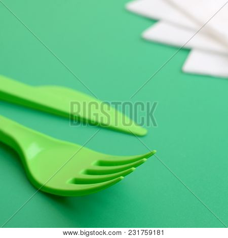 Disposable Plastic Cutlery Green. Plastic Fork And Knife Lie On A Green Background Surface Next To N