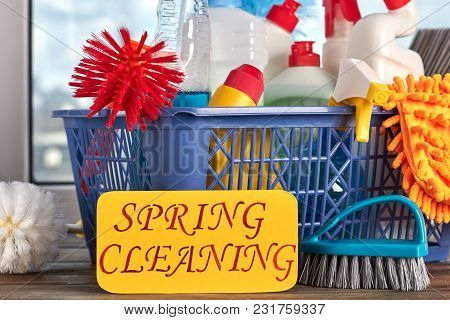 Spring Cleaning Concept With Supplies. House Cleaning Items In Basket And Paper Card With Text Sprin