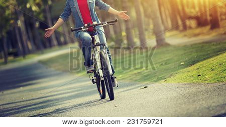 Happy Woman Cyclist Riding Bike In Spring Tropical Park