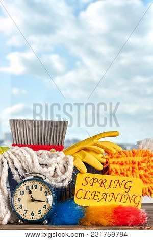 House Cleaning Supplies On Sky Background. House Cleaning Products And Alarm Clock. Time To Make Spr