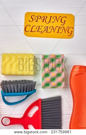 Spring Cleaning Concept With Supplies. Kitchen Sponges, Brushes And Cleaning Liquid On White Wooden