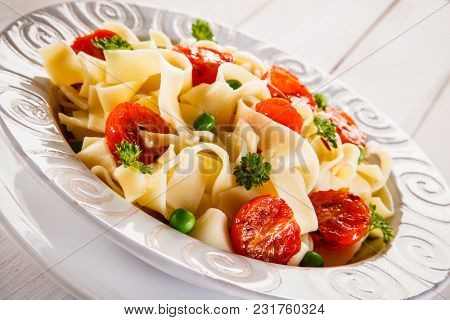 Pasta with vegetables on wooden table