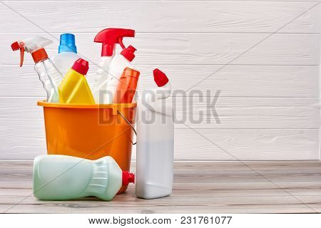 Bucket With Cleaning Supplies, Copy Space. Cleaning Supplies Kit On Wooden Background. Cleaning Serv
