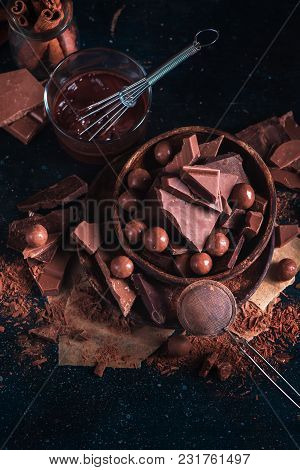 Wooden Bowl With Homemade Chocolates And Chocolate Pieces, Glazing With A Whisk, Scattered Cocoa Pow