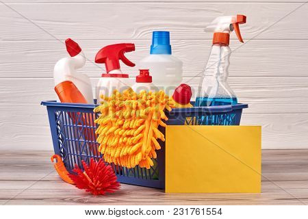 House Cleaning Products In Basket. Bottles With Cleaning Liquid, Brush, Microfiber Glove And Blank P