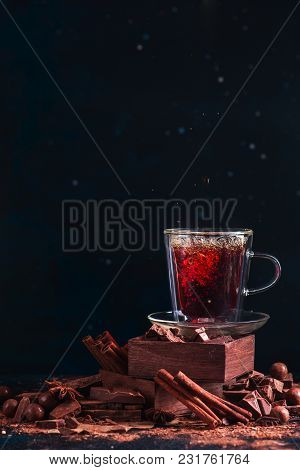 Tea In A Double Wall Cup On A Stack With Spice Boxes. Cinnamon, Broken Chocolate Pieces, Cocoa Powde