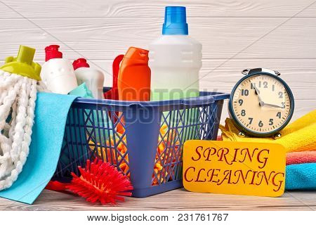 Basket With Cleaning Items On Wooden Background. Set Of Products For House Cleaning And Alarm Clock.