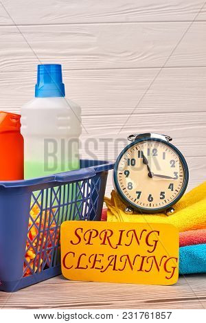 Household Cleaning Products And Alarm Clock. Detergent Bottles And Cleaning Supplies In Plastic Bask