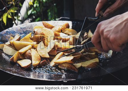 Pieces Of Potatoes Are Fried In Boiling Oil. Cooking Process. The Street Food.
