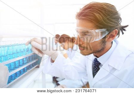 Laboratory assistant in goggles and a lab coat with a test tube