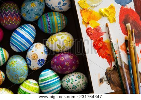 Easter eggs, brushes and paints on wooden background
