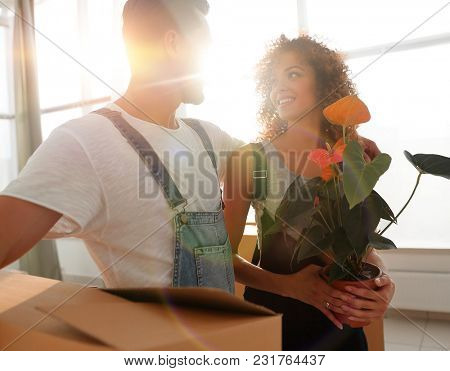 Close-up of a beautiful young couple is carrying things into a n