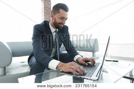 Successful man working on laptop in modern office