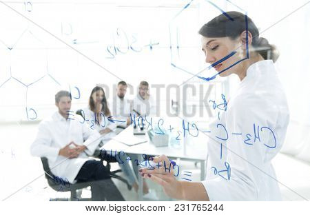 view through the transparent Board. female biochemist makes a report to colleagues