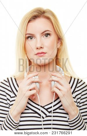 Young blond serious woman is wearing headphones around her neck
