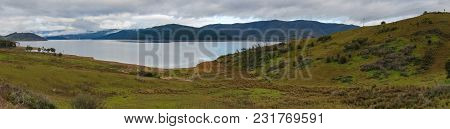 Panorama Of Picturesque Lake And Forest Covered Mountains On The Background