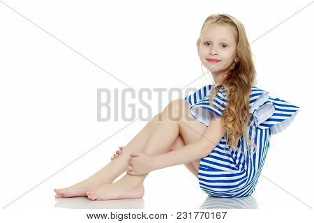 Adorable Little Blond Girl In Very Short Summer Striped Dress.she Sits On The Floor Barefoot, Turnin