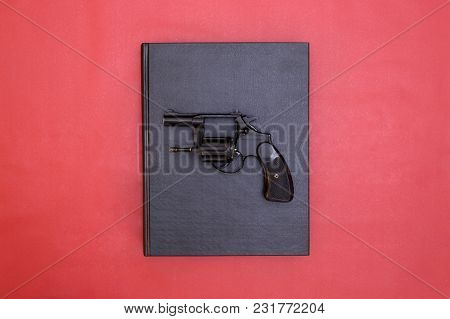 Book And Gun On Red Background