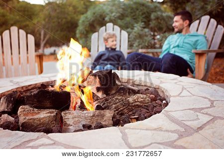 View Of Firepit And Happy Smiling Family Of Two, Father And Son, Enjoying Time Together In The Backg