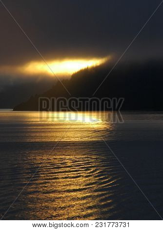 Light From The Setting Sun Falls Through A Cloudy Sky To Onto A Lake, Turning The Ripple On The Wate