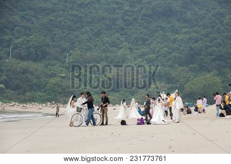 Shenzhen, China, 2011-11-26: Numerous Chinese Couples In Wedding Dresses Posing At The Beach For The