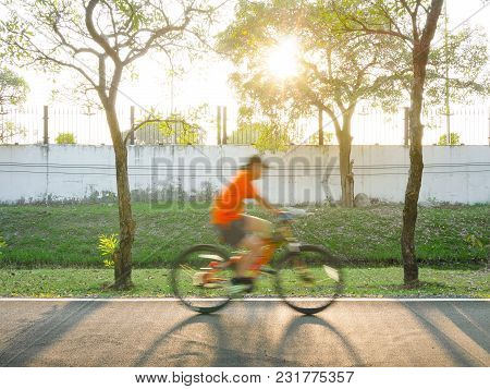 Blurred Young Man Cycling On Bike Lane In The Park At Sunset