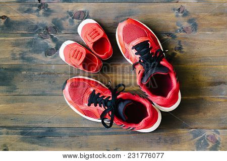 Two Red Sport Running Shoes Or Sneakers Of Mother Or Father And Child On Wooden Background,use For F