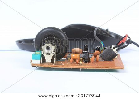 The Dusty Circuit Board And Rotating Wheel Inside An Old Computer Mouse.