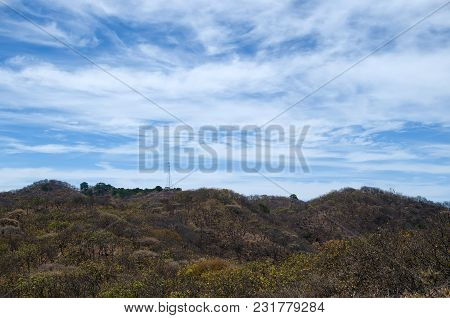View To The Hills Covered With Forest, Electric Poll And Blue Cloudy Sky