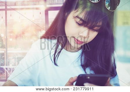 Asian Woman In A Coffee Shop Touches The Smartphone Screen, Using Send A Message To A Friend Social
