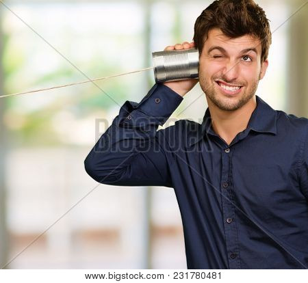 Young Man Listening From Tin Can Phone, Indoors