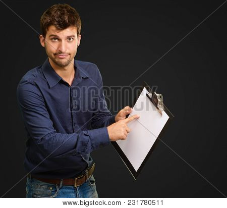 Young Man Pointing On Clipboard Isolated On Black Background