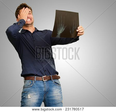 Young Man Holding X Ray Report Gesturing  On Grey Background
